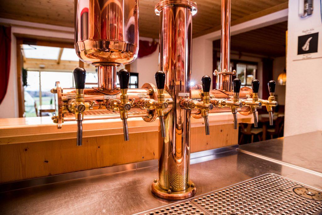 Durch die Schankanlage im gemütlichen Gastraum vom Restaurant Kugler Alm fließt das Bier der bayrischen Schlossbrauerei Maxlrain