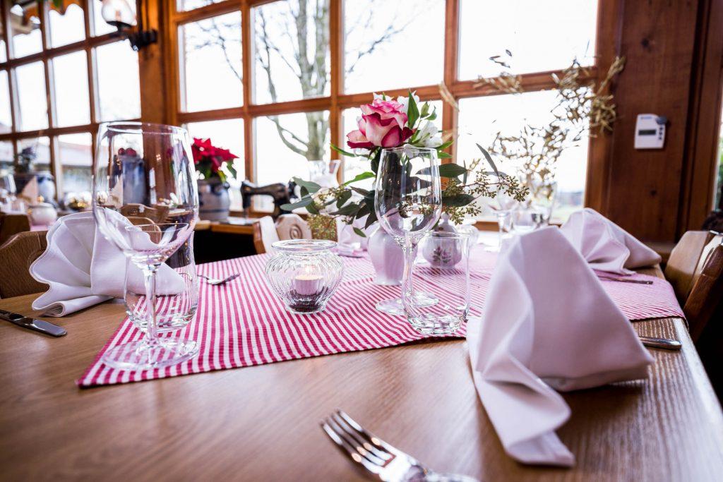 Mit Servietten als Fächer eingedeckter Tisch im großen Saal der Kugleralm Ebersberg