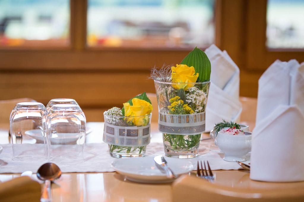 Hübsche kleine Farbtupfer mit frischen Blumen als Highlights der Tischdeko bei einer Taufe auf der Kugleralm in Ebersberg