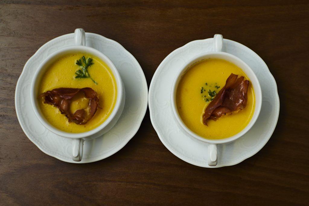Cremige Kürbissuppe aus Hokkaido Kürbs mit Bacon und Petersilie garniert