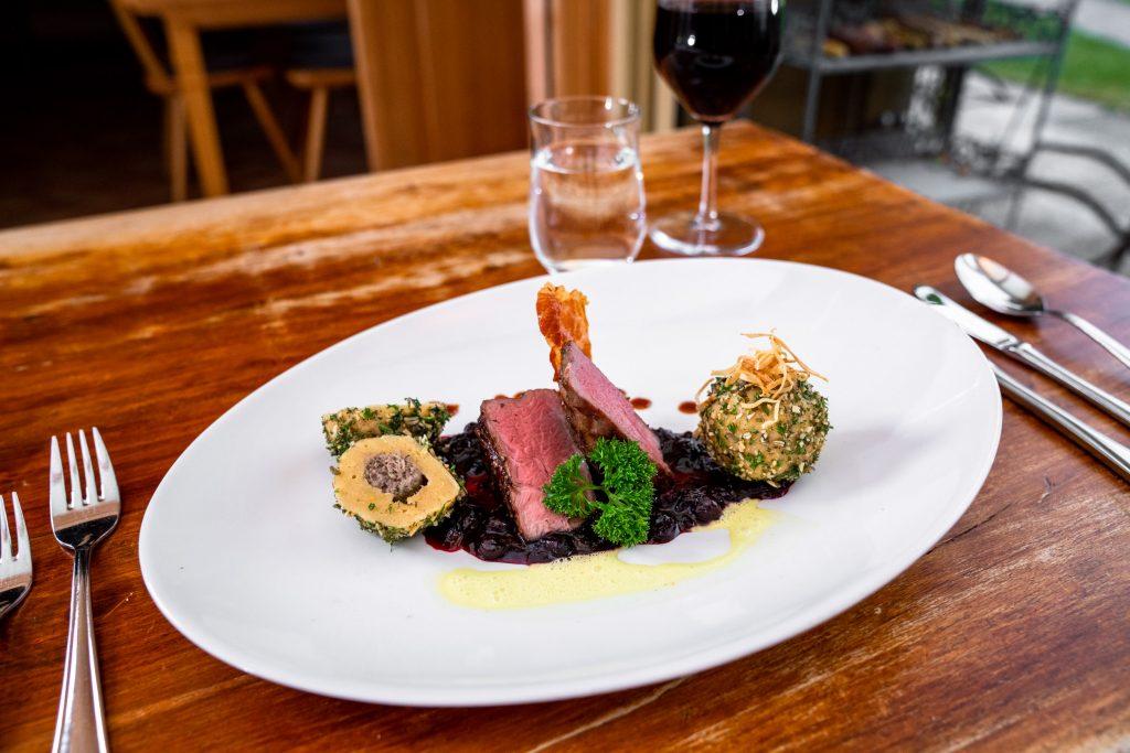 Als Hauptgang rosa gebratenes Filet vom Hirsch auf Chutney von schwarzen Johannisbeeren mit gefüllten Topfenknödeln