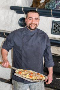 Unser Koch Georg präsentiert stolz einen unserer hausgemachten Flammkuchen