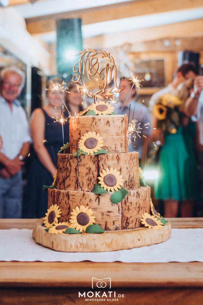 Auch die Hochzeitstorte passte perfekt zum Thema Sonnenblumen bei der Sonnenblumen Hochzeit auf der Kugler Alm Ebersberg